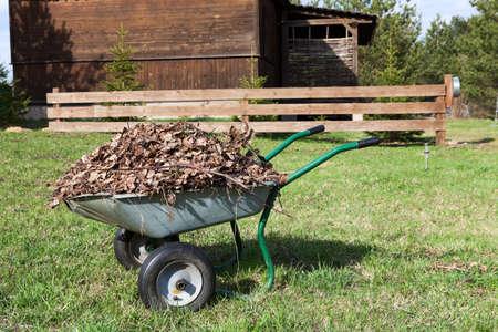 Brouette avec des feuilles sèches debout dans la cour rurale près de la maison en bois