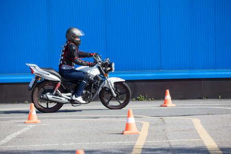 Vrouw L-driver het doen van oefeningen rond kegels op de motor in vaardigheidstraining motordrome. Russische chauffeur scholen Stockfoto