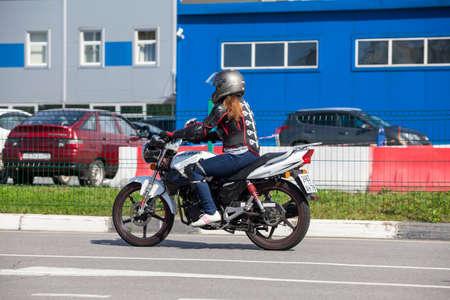 beginner: ST. PETERSBURG, RUSSIA - CIRCA AUG, 2016: Beginner rides on the motorbike on the skill training motordrome. Russian driver school