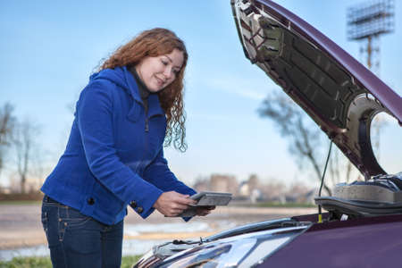 only 1 woman: Young woman making repair works of broken car with information throuth the tablet pad and Internet