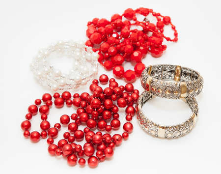 Bijouterie on a white background: red and pearl beads, gold bracelets