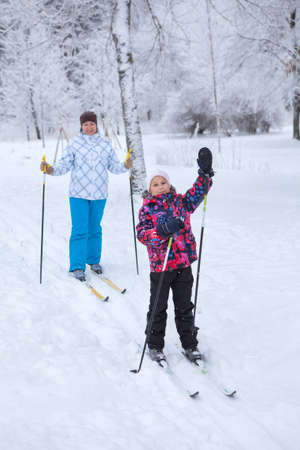 ski walking: Walking on ski in winter forest, Caucasian woman with child skiing together