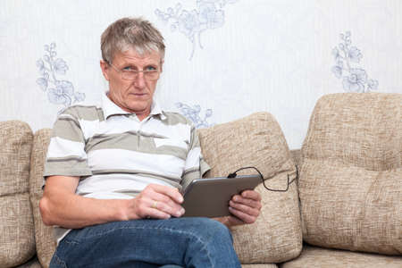 one senior man only: Senior man using tablet pad in domestic room sitting on sofa, copyspace