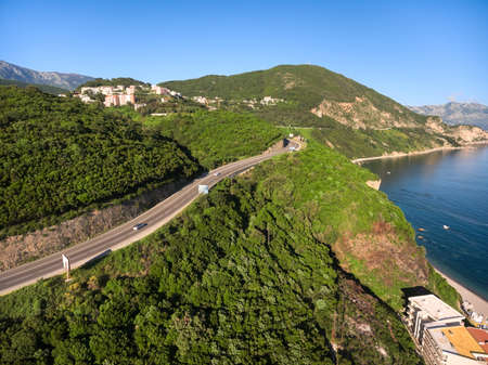 blue sea: Jaz beach coastline with Adriatic highway passing around hills. Cars driving on road. Budva municipality, Montenegro