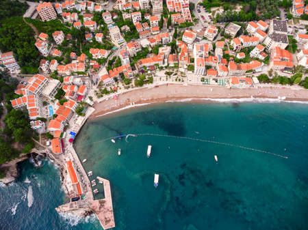 sea of houses: City sea shore with beach and pier next to dwelling houses. Town of Petrovac. Adriatic sea. Montenegro. Aerial view Stock Photo