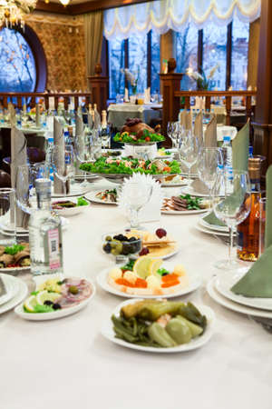 bebidas alcohÓlicas: Celebratory long table with cold snacks and alcoholic beverages in a restaurant