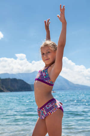 Sporty Caucasian young blond girl portrait. Standing on sea in swimwear, arms stretching up.