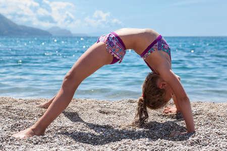 acrobacia: posición del puente de gimnasia. Niña en la toma de traje de baño de yoga en la arena Foto de archivo