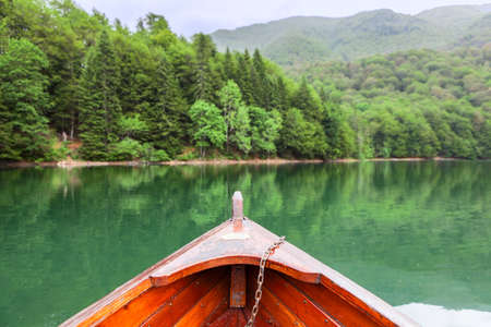 evergreen forest: View at the green water and evergreen forest on the Biograd lake from wooden row boat. Montenegro, Europe