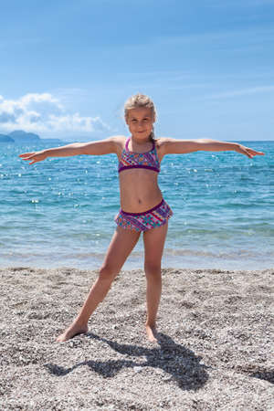Pretty Caucasian girl in swim suit standing on seashore with arms stretching lateral. Full lenght