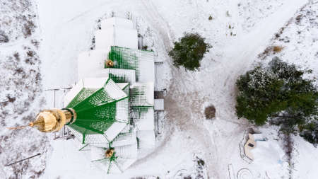 kirk: Aerial view at the green domes of wooden church covered with snow at winter. Golden cross is on the top. Stock Photo