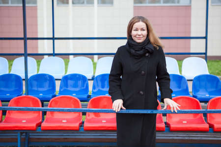 Russian fan a pretty woman in black coat standing against national colors stadium seats Stock Photo