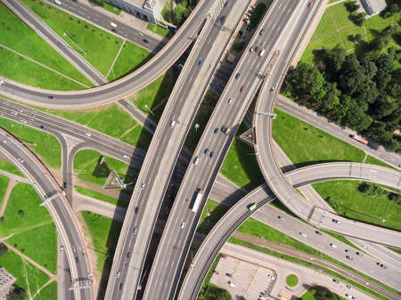 junctions: Aerial view at junctions of interchange of urban highway. Vehicles drive on roads. Russia Stock Photo