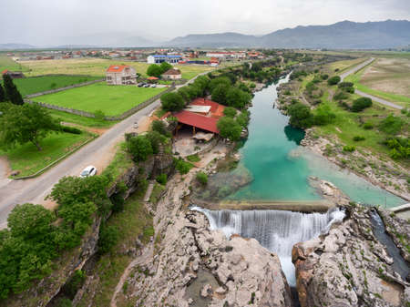 Canyon of the Cijevna river crossing the valley with waterfall Montenegrin Niagara. Podgorica, Montenegro. Aerial view