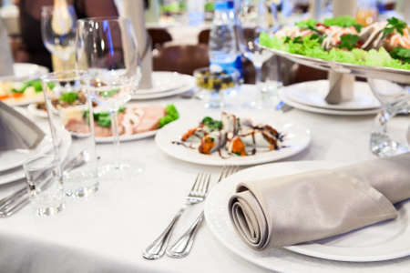 A celebratory table with cold dishes, white plates, cutlery and napkins Stock Photo