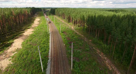 Freight train coming at the double line railway with electric poles in evergreen forest, aerial view ahead to locomotive