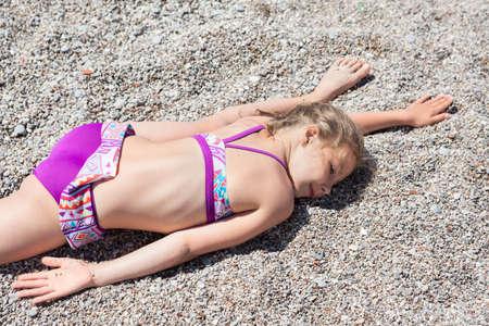 traje de baño: chica de raza blanca pequeño que pone en la arena en el ejercicio de división transversal, playa del mar