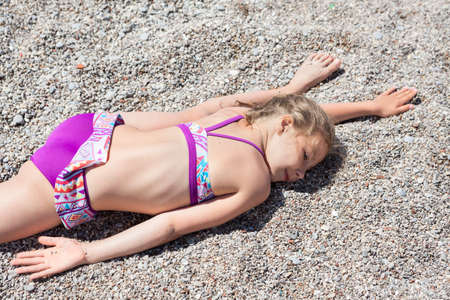 Little Caucasian girl laying on sand in cross split exercise, sea beach