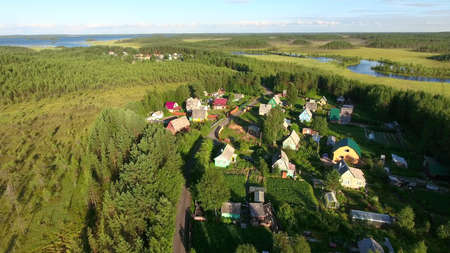 Russian summer village with wooden houses at sunset. Flying over roofs. Forests of northern Karelia, Russia Reklamní fotografie