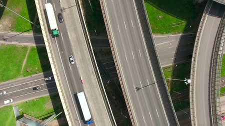 encircling: Top view at curvers and lines of city highway. Two semitrailer trucks drive on road. Summer. Russia