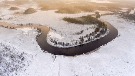 subset: Aerial view at wintry river turn with open water and snow covered shores and swamps. Forests of Karelia, Russia.
