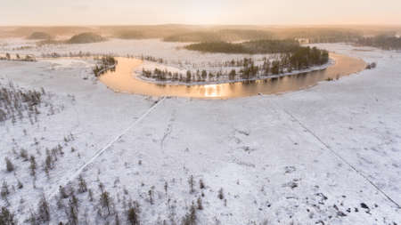 subset: Turn of the forest river with sunset light reflection in open water. Winter swamp field with pines trees. Aerial view, Karelia, Russia