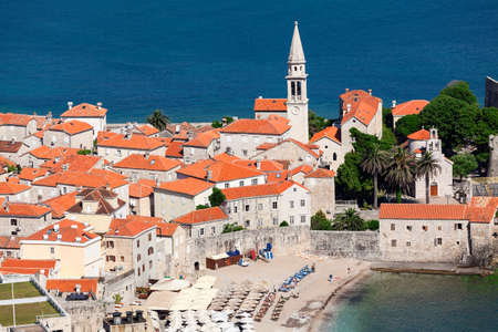 sea of houses: Bell tower of the Old Town of Budva city and Ricardova Glava beach. Aerial view with houses roofs. Adriatic sea. Montenegro