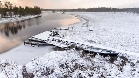 Snowy planked footway to the river turn with snow covered shore. Small wooden pier with row boats. Sunset at evening. Karelia, Russia Stock Photo