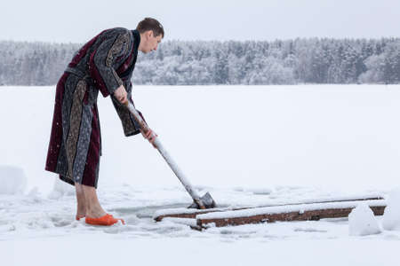 Young Caucasian man in bathrobe preparing ice-hole for dipping at winter season. Russia