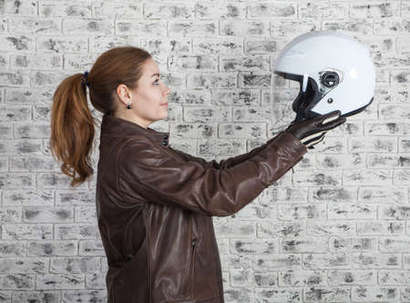 Beautiful motorcyclist selects white open helmet while holding in stretching arms, brick wall background, side view Banque d'images