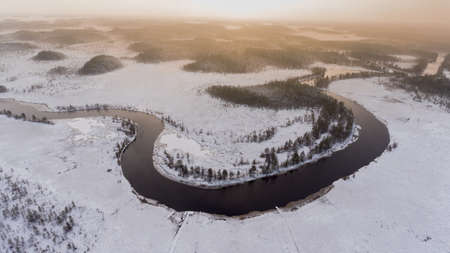 subset: Polar night is on wintry river turn with open water and snow covered shores. Forests of Karelia, Russia. Aerial view