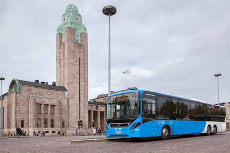 bilding: HELSINKI, FINLAND - CIRCA SEP, 2016: Blue passenger city bus is near bilding of railway and metro station. The Rautatientori is the local point of all urban public transport in the Kluuvi