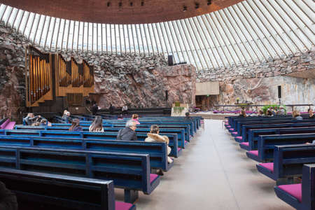 church people: HELSINKI, FINLAND - CIRCA SEP, 2016: Hall with natural lighting, benches and the stage. The Finnish church Temppeliaukio. The temple is carved into the rock. Editorial