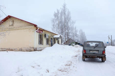 cold season: VALDAY, RUSSIA - CRICA JAN, 2016: Car stops near one-storeyed house of grocery store on rural wintry road. Small shop is in the Russian countryside. Cold winter season