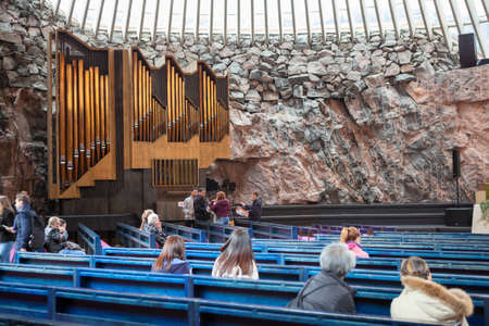HELSINKI, FINLAND - CIRCA SEP, 2016: Visitors sit on benches in the church Temppeliaukio. The pipe organ is near stone wall. The temple is carved into the rock Editorial