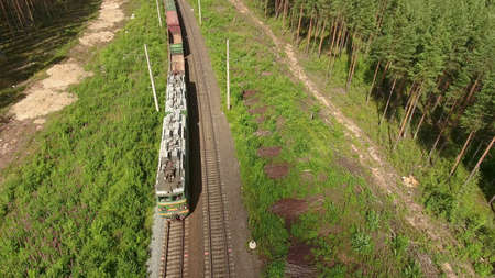 towards: KARELIA, RUSSIA - CIRCA AUG, 2016: Freight train passes at the double line railroad with electric poles in evergreen wood. Aerial view towards to locomotive. Northern Oktyabrskaya Railway