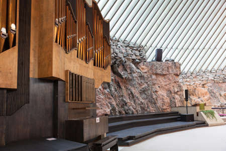 HELSINKI, FINLAND - CIRCA SEP, 2016: The pipe chair organ is near stony wall in the Finnish church Temppeliaukio. The temple is carved into the rock.