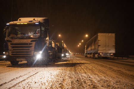 NOVGOROD, RUSSIA - CIRCA NOV, 2016: Long traffic jam is on wintry federal road M10 at night time. Freight trucks stand Moscow direction due road accident at slippery turn. Editorial