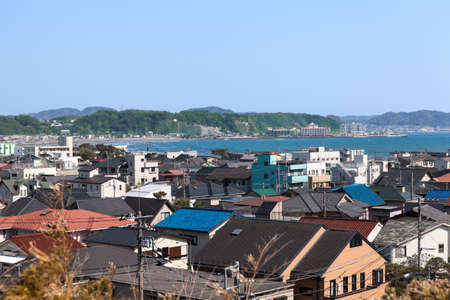 kanagawa: Top view at the Kamakura town. Houses with color roofs are on the coastline of Pasific ocean. Kamakura is a small town in Kanagawa Prefecture Stock Photo
