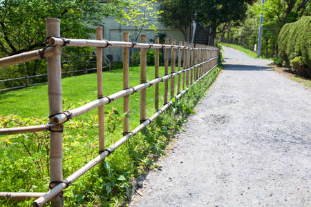yard stick: Bamboo fence is along ground road in countryside of small Japanese village. Japan Stock Photo
