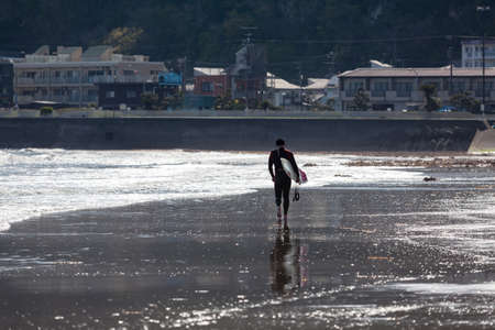 KAMAKURA, JAPAN - CIRCA APR, 2013: Japanese man a surfer steps on low tide sandbank in Yuigahama beach. The Sagami Bay is famous for wind surfing. Low season time