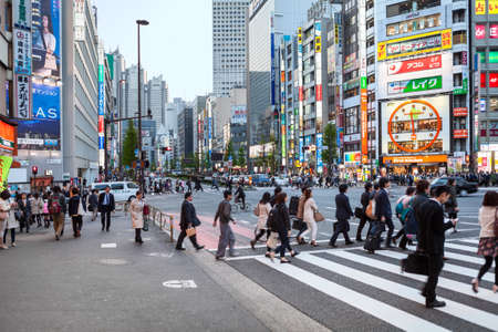 japanese people: TOKYO, JAPAN - CIRCA APR, 2013: Pedestrian crossroad with walking Japanese people is on Shinjuku district at evening. It is a major commercial and administrative centre Editorial