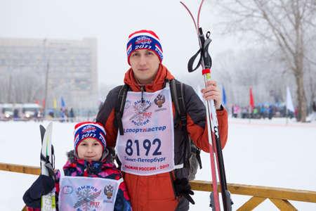 ST. PETERSBURGO, RUSIA - JAN, 11, 2017: Retrato de padre con hija con equipos de esquí de fondo. Están en los atributos oficiales como sombreros y números de babero. La carrera de esquí de masas de toda Rusia 2017