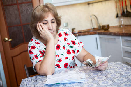 communal: Caucasian woman looks with sad at receipts for communal payment while sitting on the kitchen