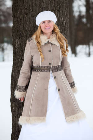 Joyful blond hair bride in fur-coat leaning back the tree in winter snowy park