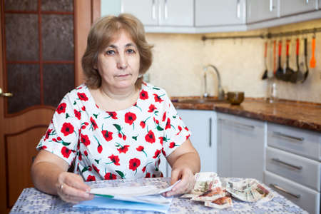 Portrait of Caucasian woman with cash money and receipts for communal payment on table
