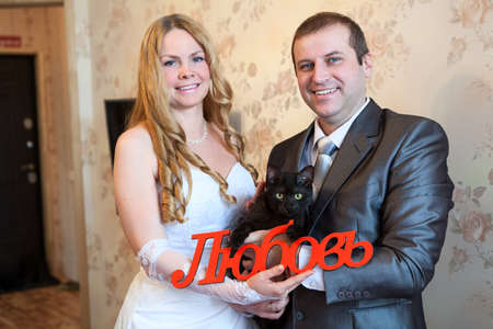 Caucasian bride and groom with black cat and word Love in Russian in hands. Empty room, housewarming