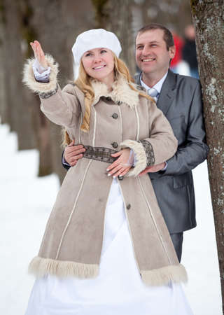 Young bride pointing with hand for groom sight. Embracing wedding couple is in winter snowy park