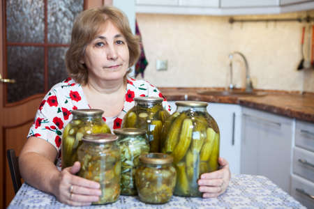Caucasian Russian middle-aged woman sits at a table in kitchen with glass jars full of pickles Imagens