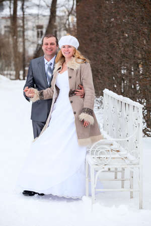 Caucasian bride and groom standing next to a white iron bench in a winter park